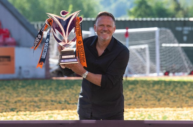 Scott Booth celebrates with the SWPL trophy after leading Glasgow City to the title earlier this year