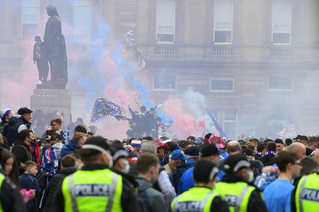 Police officers monitor as Rangers fans celebrate in George Square in Glasgow on May 15, 2021. (Photo by ANDY BUCHANAN/AFP via Getty Images)