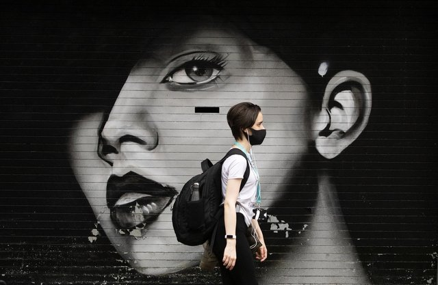 A woman wearing a protective face mask walks through Glasgow city centre. Picture: Jane Barlow/PA Wire