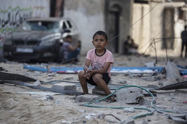 A Palestinian boy sits near buildings hit by Israeli airstrikes in the Jabaliya refugee camp, northern Gaza Strip, (Picture: Khalil Hamra/AP)