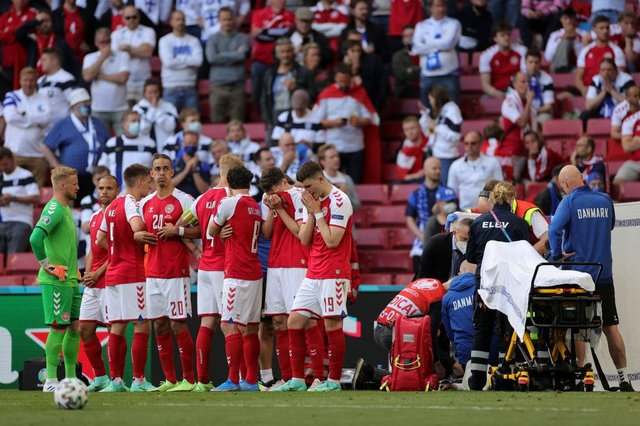 Denmark's players form a protective shield around Christian Eriksen as he receives medical attention. Picture: SNS