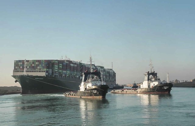The Ever Given, a Panama-flagged cargo ship is pulled by Suez Canal tugboats, in the Suez Canal, Egypt as it is set free (Suez Canal Authority via AP).