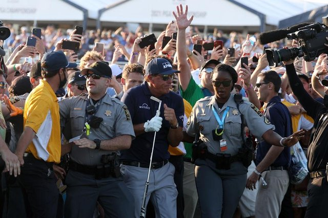 Phil Mickelson is assisted by security as he is followed up the 18th fairway by a gallery of fans in the final round of the 2021 PGA Championship at Kiawah Island. Picture: Patrick Smith/Getty Images.