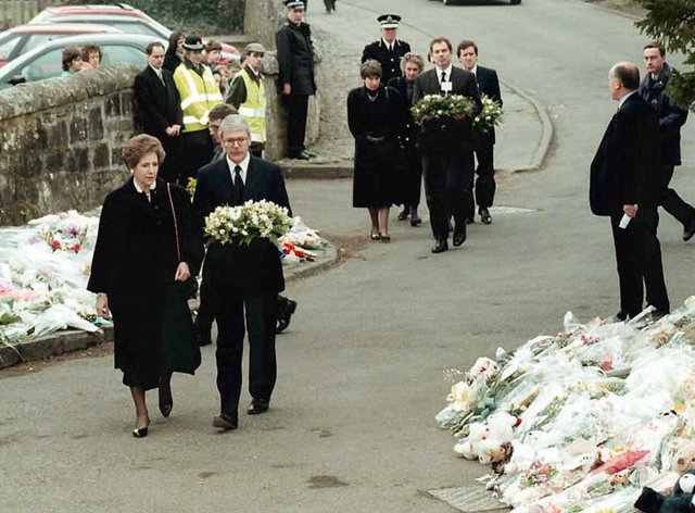 Prime Minister John Major and opposition leader Tony Blair bring their floral tributes to Dunblane Primary School after the shooting (Getty Images)
