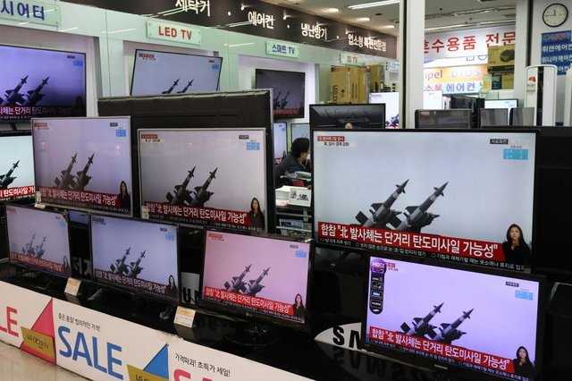 TV screens show a news program reporting about North Korea's ballistic missiles. The missiles fell into the Sea of Japan on Thursday, March 25.