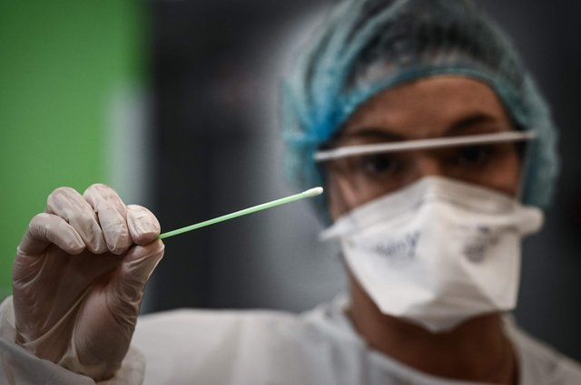 A medical professional holds a swab used for a rapid-result Covid-19 antigen test. Picture: Philippe Lopez via Getty Images