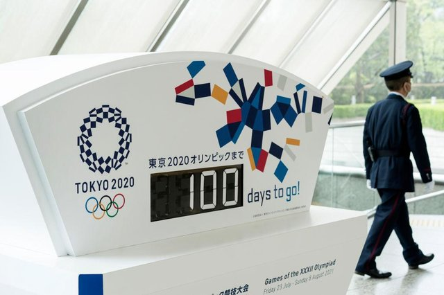A security guard walks past a display showing 100 days to go to the Olympic games at the Tokyo Metropolitan Government.