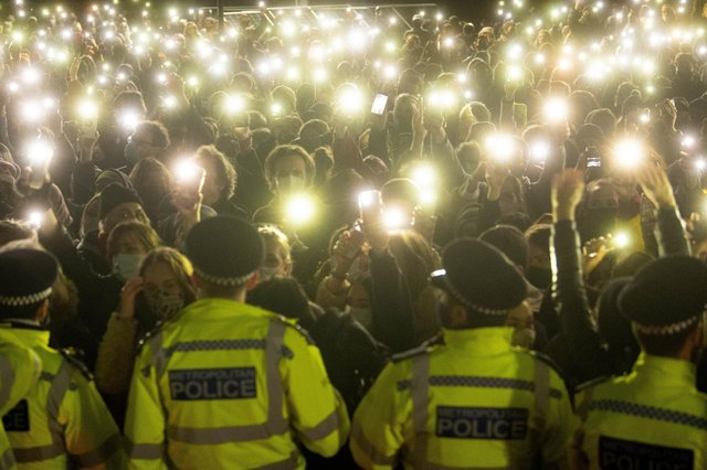 People in the crowd turn on their phone torches as they gather in Clapham Common, London