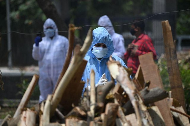 A relative wearing Personal Protective Equipment (PPR kit) performs the last rites before the cremation of a person who died due to the Covid-19 coronavirus at a cremation ground in New Delhi on May 11, 2021. (Photo by SAJJAD HUSSAIN/AFP via Getty Images)