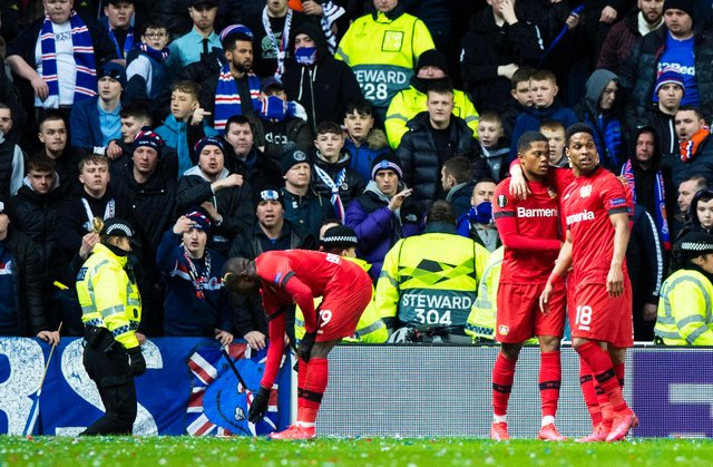 Bayer Leverkusen's Moussa Diaby (L) picks up a bottle during the Europa League last 16 first leg against Rangers at Ibrox.