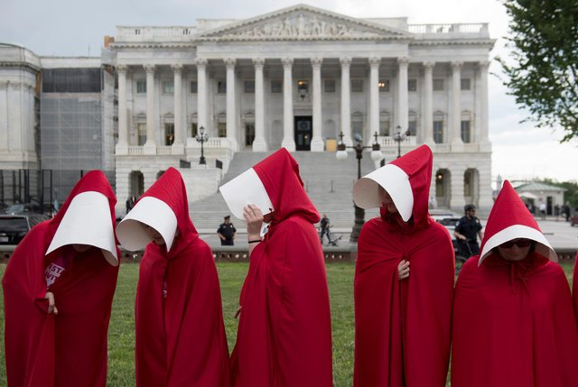 Supporters of sexual health body Planned Parenthood dress as characters from The Handmaid's Tale as they protest outside the US Senate (Picture: Saul Loeb/AFP via Getty Images)