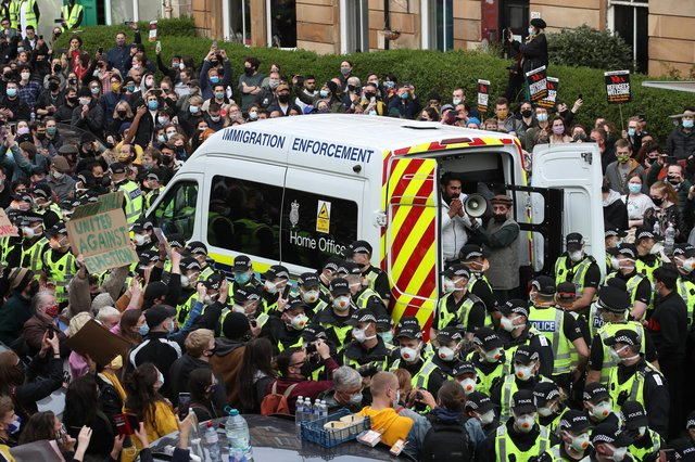 One of two men are released from the back of an Immigration Enforcement van accompanied by Mohammad Asif, director of the Afghan Human Rights Foundation, in Kenmure Street, Glasgow which is surrounded by protesters. Picture date: Thursday May 13, 2021.