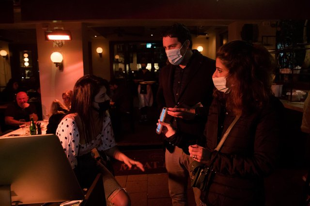 A couple present a 'Green Pass' vaccination certificate to staff at a bar in Tel Aviv, Israel, where a controversial Covid passport system has been introduced (Picture: Amir Levy/Getty Images)
