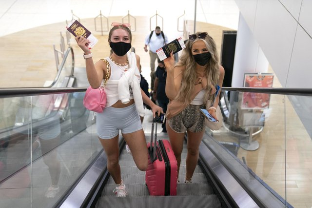 Friends Poppy (left) and Shannon, both aged 20 and from Glasgow, head towards the departure gate at Glasgow Airport after checking in for their flight to Ibiza.