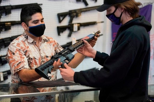 A customer considers buying a custom made AR-15-style rifle in a gun shop in the United States