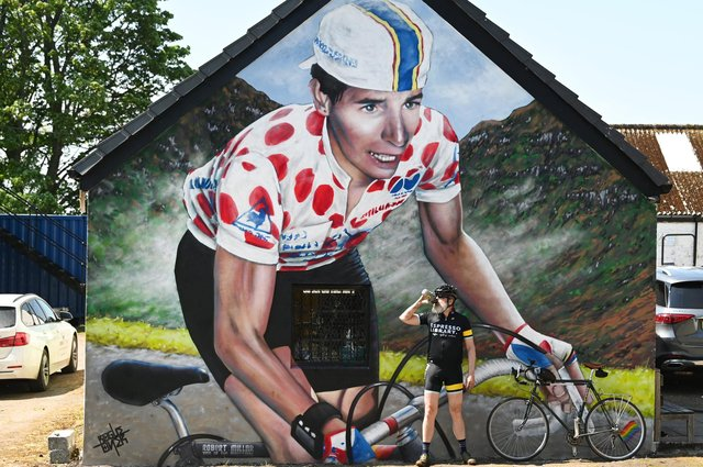 A cyclist takes a break at the new mural, created by Scottish artist Rogue One (aka Bobby McNamara)