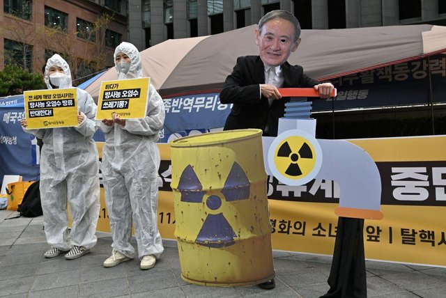 South Korean environmental activists wearing protective clothing and a mask of Japan's Prime Minister Yoshihide Suga perform during a protest against Japan's decision on releasing Fukushima wastewater, near the Japanese embassy in Seoul on April 13, 2021.