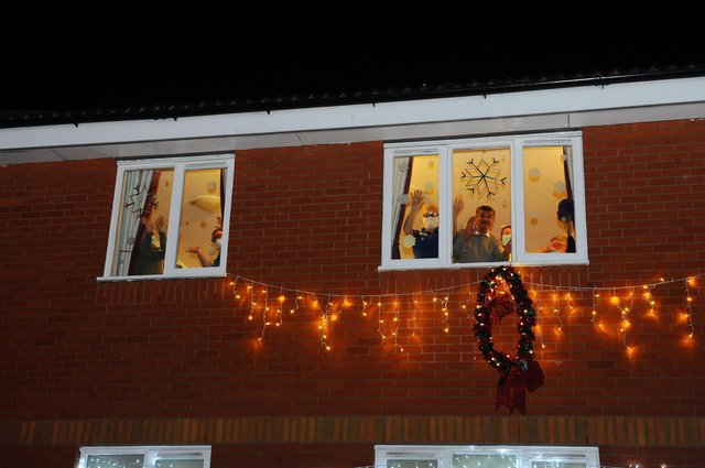People wave from inside a care home during the Christmas period (Picture: Michael Gillen)