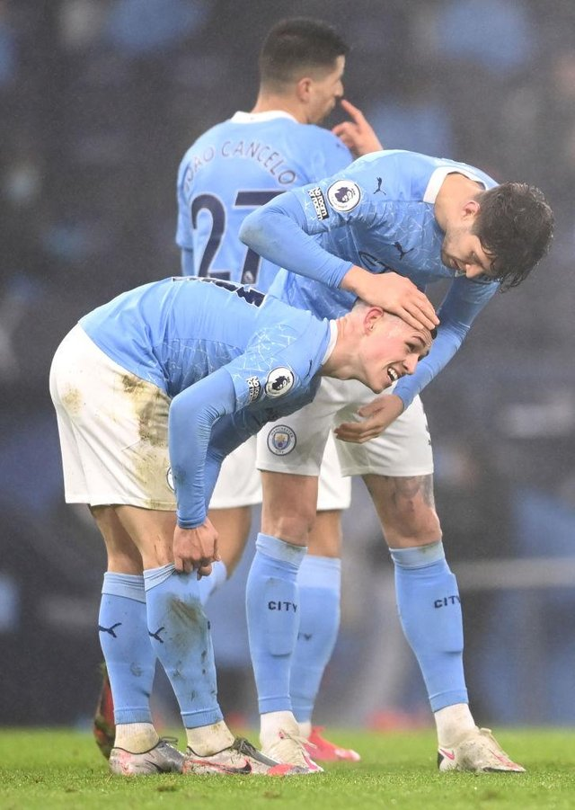 Phil Foden of Manchester City is congratulated by teammate John Stones after scoring on January 13