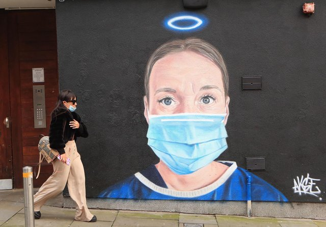 A woman walks past a mural in Manchester city centre. Cities in northern England and other areas suffering a surge in Covid-19 cases may have pubs and restaurants temporarily closed to combat the spread of the virus. Picture: Danny Lawson/PA Wire
