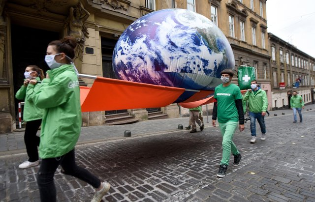 Greenpeace activists carry a giant balloon representing planet Earth  (Photo by DENIS LOVROVIC/AFP via Getty Images)