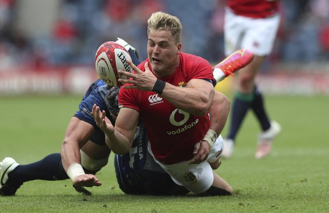 Duhan van der Merwe, who scored a try on his Lions debut, is tackled by Japan's Lappies Labuschagne.