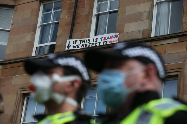 A man holds a sign out of a window above police guarding an immigration van in Kenmure Street, Glasgow which is surrounded by protesters.