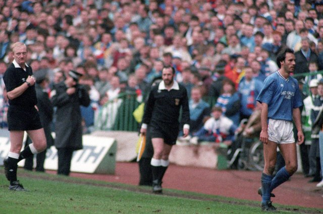 Rangers striker Mark Hateley leaves the field having been shown the red card by referee Andrew Waddell.