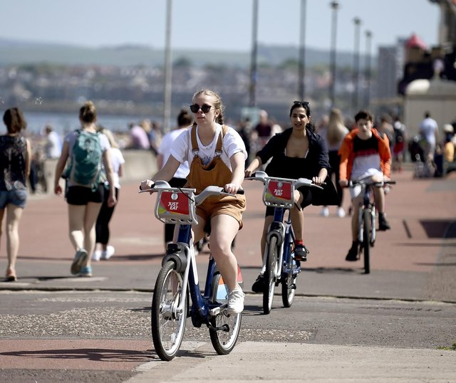 Locals enjoy sunny weather at Portobello Beach, with warm weather and bright sunshine expected in the capital this weekend.