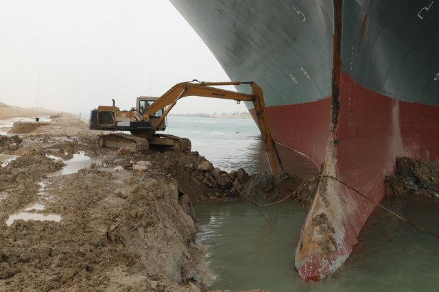 A digger clearing sand from beside the grounded Ever Given on Thursday. Picture: Suez Canal Authority/PA