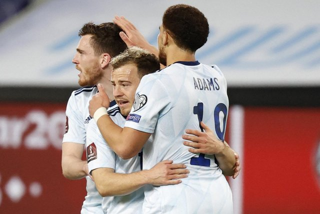 Scotland's forwrad Ryan Fraser (C) is congratulated for his goal by teammates Che Adams (R) and Andrew Robertson during the 2022 FIFA World Cup qualifier group F football match between Israel and Scotland at Bloomfield stadium in the Israeli Mediterranean coastal city of Tel Aviv on March 28, 2021. (Photo by JACK GUEZ / AFP) (Photo by JACK GUEZ/AFP via Getty Images)