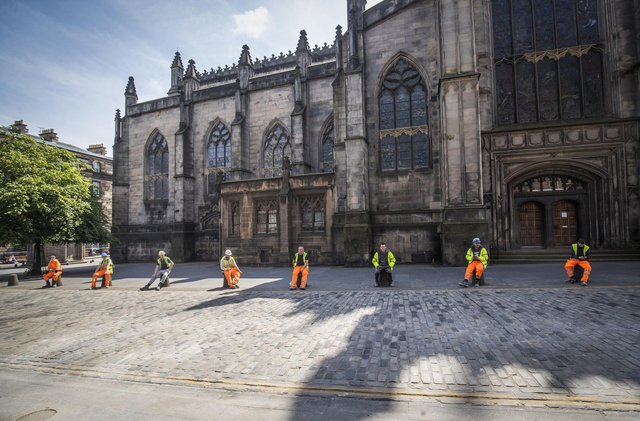 Construction workers comply with social distancing during their break along Edinburgh's Royal Mile.