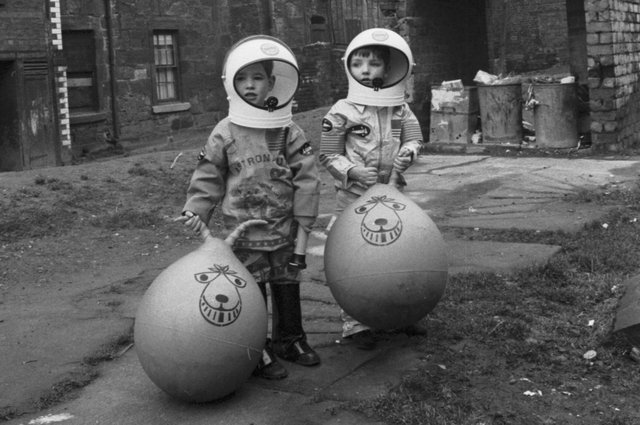 Little boys show off their Xmas presents (including astronaut suits and Space Hoppers) in Crown Street in the Gorbals area of Glasgow in December 1970.