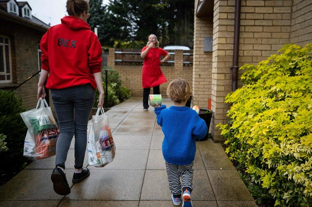 A child helps a member of staff to carry food donations.