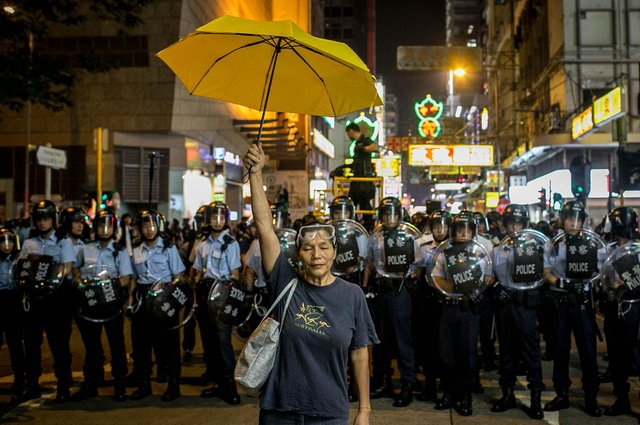 A pro-democracy activist holds a yellow umbrella in front of a police line in Hong Kong (Picture: Chris McGrath/Getty Images)