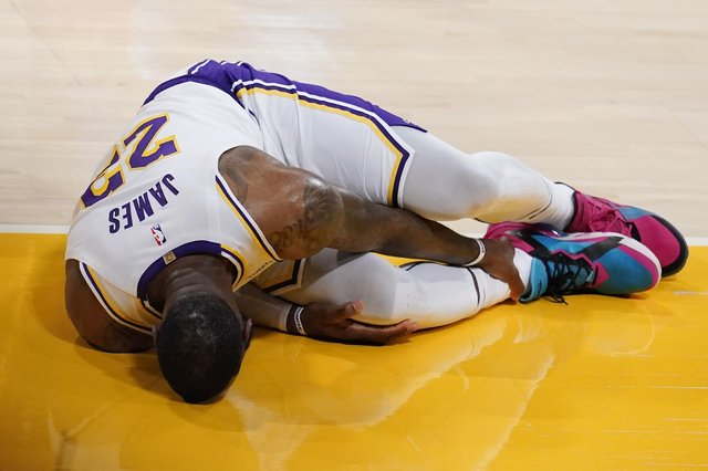 Los Angeles Lakers forward LeBron James holds his ankle after going down with an injury during the first half of the game against the Atlanta Hawks. Picture: Marcio Jose Sanchez/AP