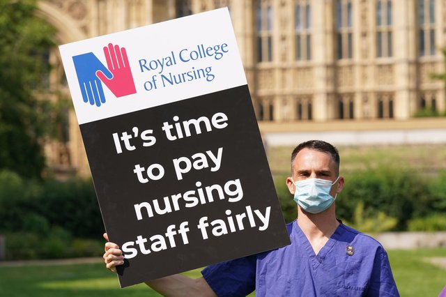 A nurse with a placard outside the Royal College of Nursing in Victoria Tower Gardens, London. Picture Jonathan Brady/PA Wire