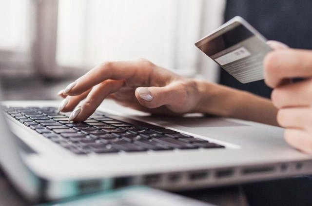 A stock image of a person at a computer with their bank card.