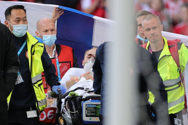 Christian Eriksen is pictured awake on a stretcher as the emergency services remove him from the pitch after administering treatment