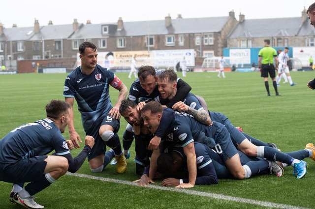 Gozie Ugwu is in there somewhere as he and his teammates celebrate his decisive goal in the 2-0 win v Dunfermline (Photo by Paul Devlin / SNS Group)