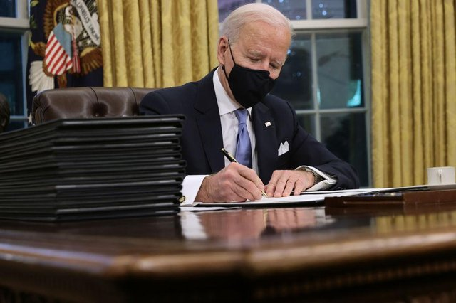 President Joe Biden prepares to sign a stack of executive orders in the Oval Office just hours after his inauguration on 20 January 2021 (Photo: Chip Somodevilla/Getty Images)