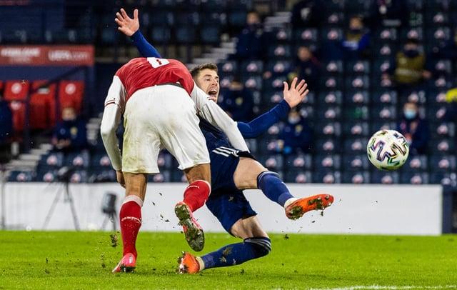 Ryan Christie is bundled to the ground by Austria's Stefan Ilsanker.
