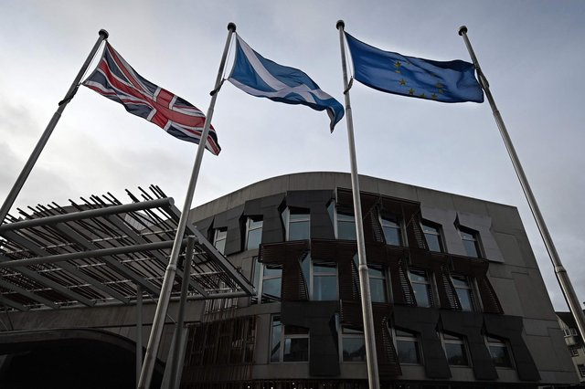 The Union Flag, Saltire of Scotland and EU flag fly outside the entrance to the Scottish Parliament building (Picture: Andy Buchanan/AFP via Getty Images)