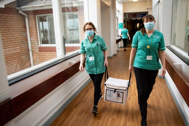 Pharmacists transport a cooler containing the Moderna vaccine, at the West Wales General Hospital in Carmarthen, ahead of delivery of the first Moderna vaccinations in the UK.
