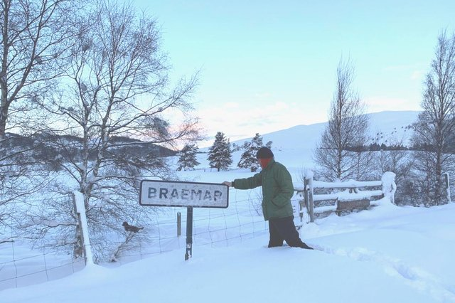 Simon Blackett, who is 6ft7in, knee-deep in snow next to the Braemar sign picture: supplied