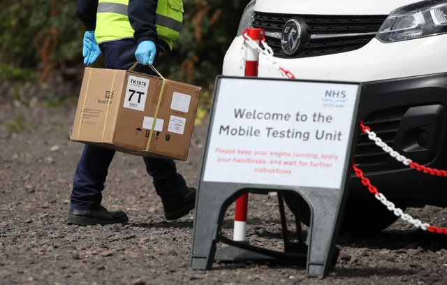Staff from the Scottish Ambulance Service carry boxes of test kits at a mobile Covid testing unit. Picture: PA Media.