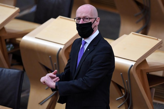 Deputy First Minister John Swinney, wearing a face mask, arrives in the chamber to update MSPs at the Scottish Parliament in Holyrood, Edinburgh.