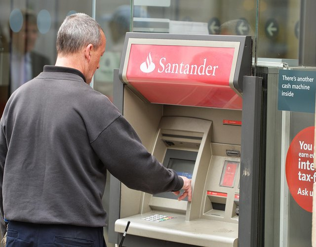 A man using a cash machine outside a branch of Santander in central London. Santander has announced it will be permanently closing 111 branches in the UK picture: John Stillwell/PA