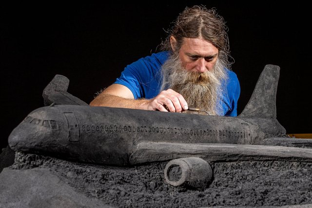 Artist Jamie Wardley working on one of his black sand sculptures commissioned by train operator LNER. Picture: Charlotte Graham
