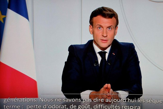 French President Emmanuel Macron is seen on a TV screen in Paris on October 28, 2020, as he delivers an evening televised address to the nation, to announce new measures aimed curbing the spread of the Covid-19 pandemic. (Photo by LUDOVIC MARIN/AFP via Getty Images)